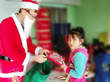 Dressed up as Santa Claus, Mitchell created holiday art with the children, decorated the Christmas tree and distributed gifts to each child
